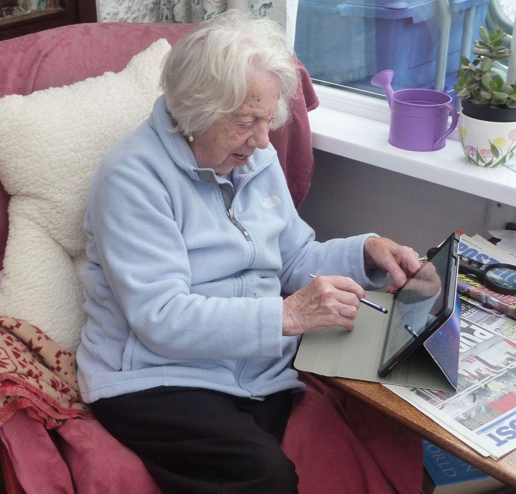 elderly lady using an ipad with a stylus